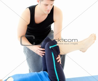 Caucasian woman exercising assited by her personal trainer