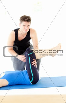 A woman exercising assited by her personal trainer