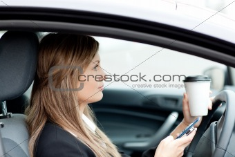 Blond businesswoman sending a text while driving