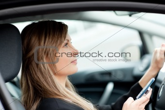 Attractive businesswoman using a mobile phone in her car