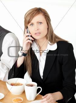 Worried businesswoman talking on phone while having breakfast