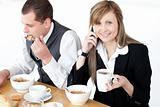 Smiling businesswoman talking on phone while having breakfast wi