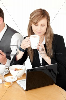 Serious businesswoman using a laptop while having breakfast