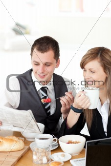 Smiling couple of business people reading a newspaper while havi