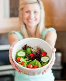 Happy woman showing a salad