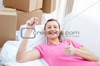 Positive woman relaxing on a sofa with boxes