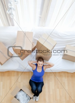 Tired woman sitting between boxes
