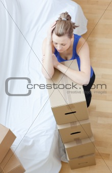 Tired woman is moving various boxes