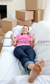 Attractive woman relaxing on a sofa with boxes