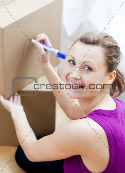 Attractive woman closing a box at home