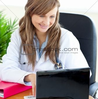 Bright female doctor working with a laptop