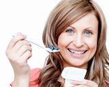 Smiling woman eating a yogurt 