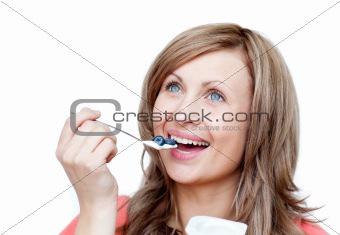 Cute woman eating a yogurt
