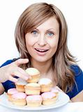 Bright woman holding a plate of cakes at home