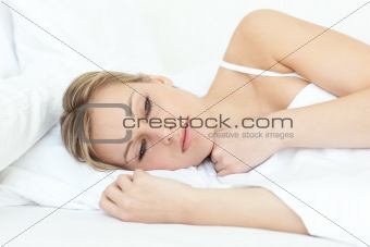 Bright woman relaxing in a bed
