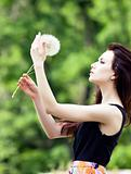Girl is blowing on dandelion.