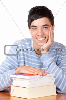 Young happy smiling male student sitting on desk with books