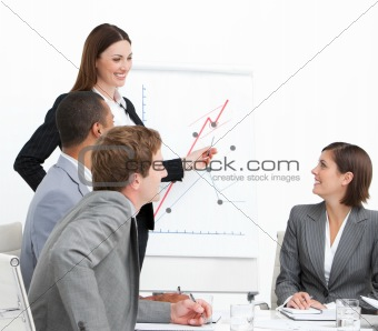 Charming businesswoman pointing at a white board while doing a presentation