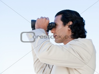 Portrait of a latin business man looking through binoculars