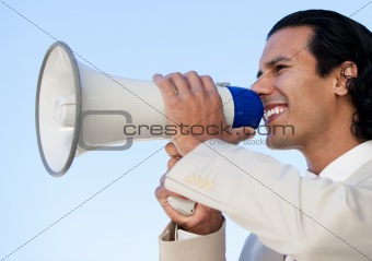 Portrait of an hispanic business man shouting through a megaphon