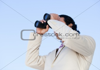 Portrait of an handsome business man looking through binoculars