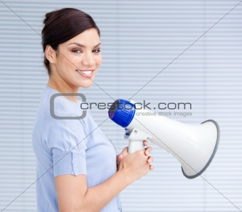 Smiling businesswoman holding a megaphone