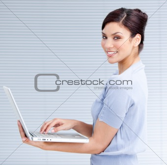 Cheerful businesswoman using a laptop