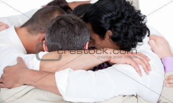 Confident business team hugging each other in a circle