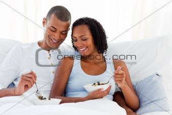 Portrait of a loving couple sitting on bed at home
