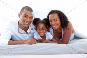 Affectionate parents and their daughter smiling at the camera