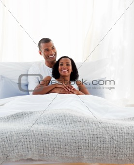 Intimate couple cuddling lying on their bed