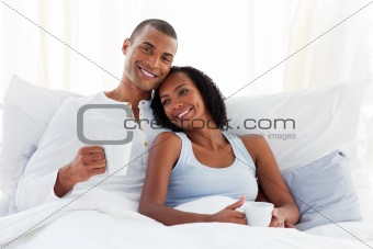 Romantic couple drinking a coffee on their bed