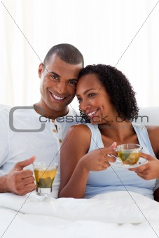 Affectionate couple drinking a cup of tea on their bed