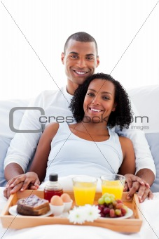 Intimate couple drinking coffee lying in the bed at home