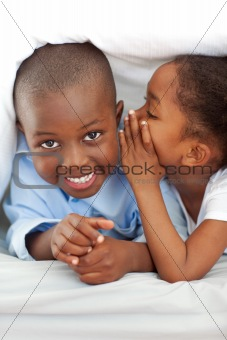 Adorable little girl whispering something to her brother