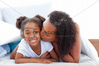 Loving woman kissing her daughter lying down on bed
