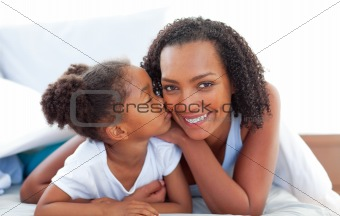 Loving little girl woman kissing her mother lying down on bed