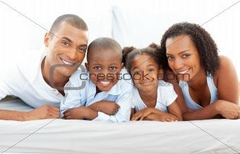 Happy family having fun lying down on bed