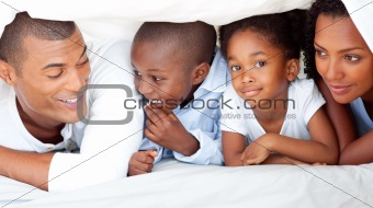 Cheerful family having fun lying down on bed
