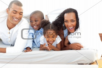 Portrait of a attentive parents with their children playing on a bed