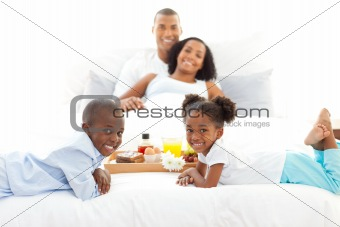 Jolly family having breakfast in the bedroom