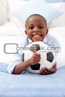 Adorable little boy holding a soccer ball