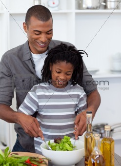 Caring father helping his son cut vegetables in the kitchen