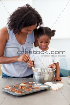 Adorable little girl preparing biscuits with her mother