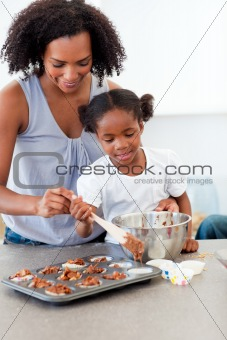 Afro-american little girl preparing biscuits with her mother