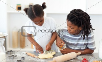 Ethnic siblings making biscuits in the kitchen