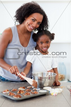 Attentive mother helping her girl cooking biscuits