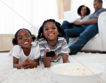 Little siblings watching television and eating pop corn