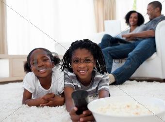 Cute siblings watching television and eating pop corn