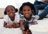 Afro american children watching television and eating pop corn